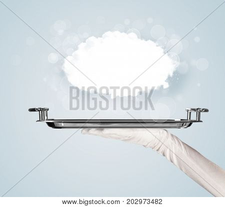 An elegant waiter business hand in white glove holding a plate with empty clear cloud in front of blue gradient background.