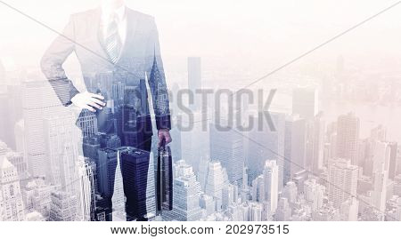 Business man standing on roof with city view in the background