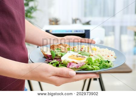 Woman holding plate with nutritious food in kitchen