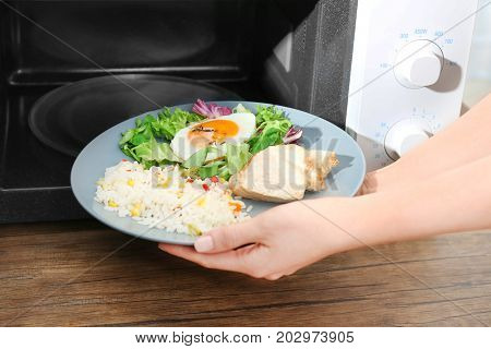Woman putting plate with nutritious food into microwave in kitchen