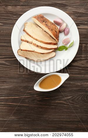 Plate with delicious sliced turkey and gravy boat on wooden table
