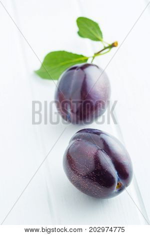 Two fresh plums on white table. Blue plums with leaves.