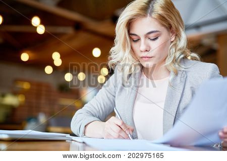 Attractive young manager writing down creative ideas concerning promising project while sitting at cozy small coffeehouse, blurred background