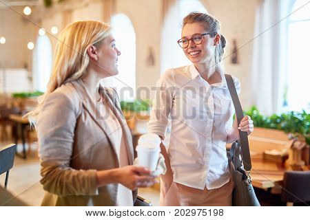 Joyful young colleague chatting animatedly with each other while standing in spacious cafe, pretty blond-haired woman holding paper cup of coffee in hands