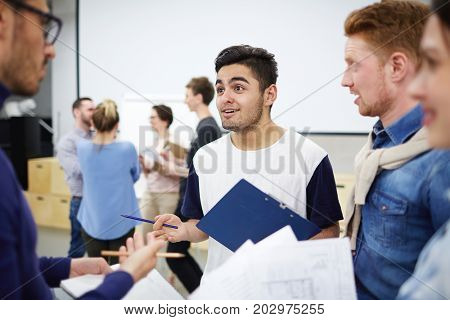 Young creative man explaining his viewpoint to groupmates