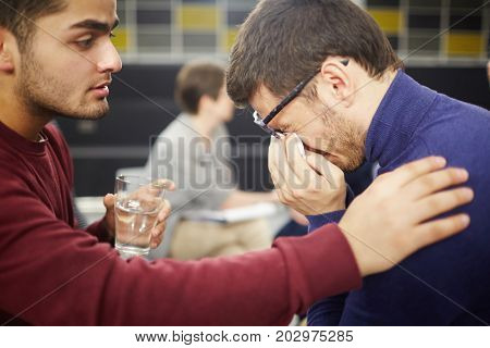 Young man crying and wiping tears with handkerchief while groupmate supporting him