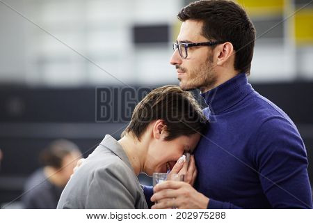 Frustrated woman crying on her friend shoulder