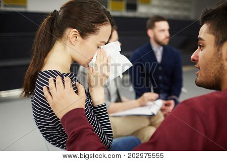 Young helpful man comforting one of groupmates during psychological session