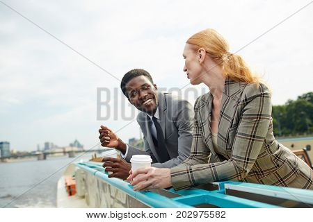 Young colleagues having drinks and interacting on steamship