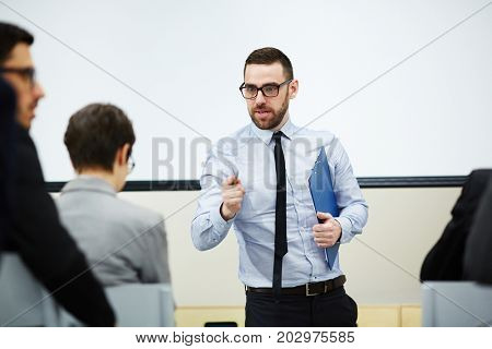 Report maker talking to audience in conference hall