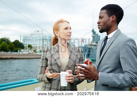 Two professionals with drinks talking on steamship by waterside