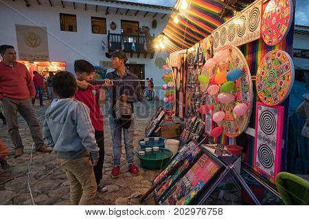 July 14 2017 Villa de Leyva Colombia: boy aiming with pellet gun to balloons in the fairground at night at the annual fiesta of the town during Honor a La Virgen del Carmen celebration
