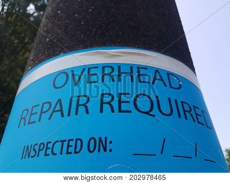 a street light with overhead repair required sign