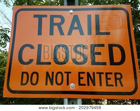 an orange trail closed do not enter sign