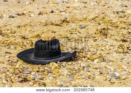 Black felt hat on pebbles on the Orient beach, Long Island NY, US
