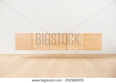 Business concept - Abstract geometric real floating wooden cube on grey background and it's not 3D render float on wood floor white background for display or montage word.