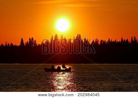 A Fishing Boat Silhouetted Against A Brilliant Orange Sky