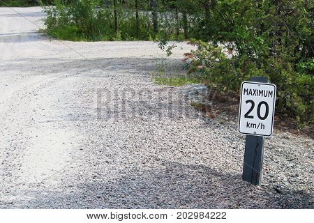 A Maximum 20 Km Per Hour Sign Along A Gravel Road