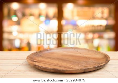 Empty wooden tray on perspective wooden table on top over blur wine bar in cafe background. Can be used mock up for montage products display or design layout.