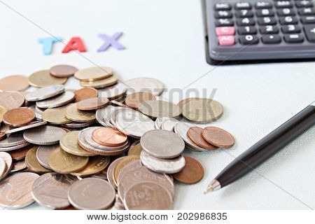 Business, finance, saving money, banking, loan, investment, taxes or accounting concept : Wooden word TAX, coins and calculator on office desk table