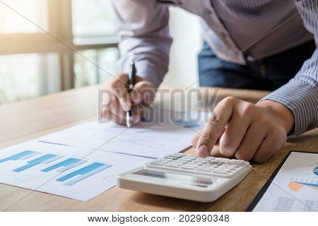 Business man or accountant working Financial investment on calculator with calculate Analyze business and market growth on financial document data graph and writing AccountingEconomiccommercial.