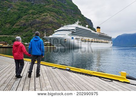 Couple of travelers look at the Cruise liner. Fjord Aurlandsfjord near Flam village, Norway
