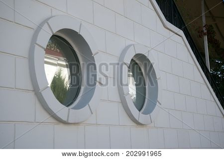 White brick wall with a two round windows