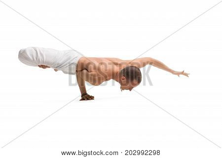 Mature shirtless muscular man wearing wide trousers practising yoga routine isolated on white