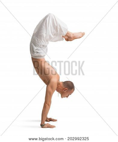 Mature shirtless muscular man wearing wide trousers doing yoga handstand isolated on white