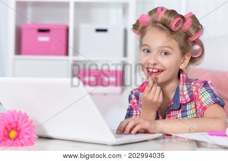 cute little girl sitting at table with laptop and beautifying  herselves