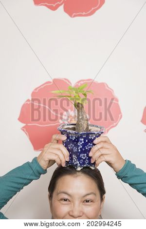 Chins woman holding potted plant on head