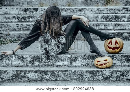 Halloween girl with pumpkins. Woman sitting on stony stairs. Fashion model in fur vest. Halloween jack o lantern symbols. Holiday celebration concept.