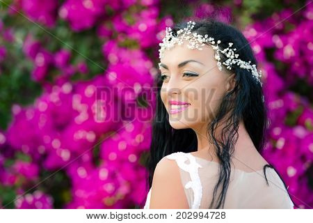 Happy woman with jewelry tiara in brunette hair. Girl smiling with stylish makeup on cute face. Bride or beauty queen on floral background. Honeymoon and summer vacation