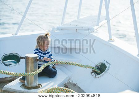 Boy kid playing with rope on yacht. Yachting and sailing concept. Little child sitting and berthing rope on white boat. Baby care and childhood. Travel and summer vacations.