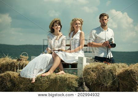 Happy women or girls reading books on bench. Man or macho with camera on cloudy sky. Friends or people relaxing on sunny day on nature. Hobby and lifestyle concept. Summer vacation and wanderlust.