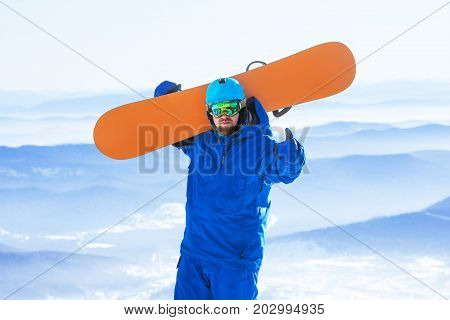 Happy man with snowboard in hands stands on mountain valley backdrop. Snowboarder or snowboarding concept