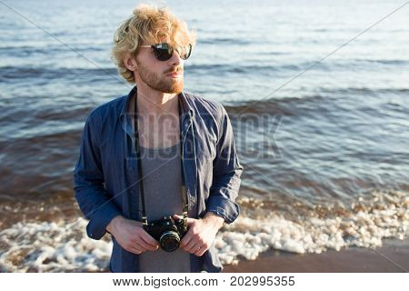 Young man with photocamera spending summer vacation by seaside
