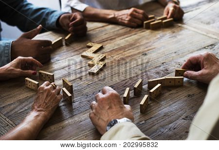 Group of people playing domino game on wooden table