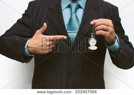 Business man showing by finger at the time on a pocket watch. Time is money concept. Being late to work concept. Work discipline.