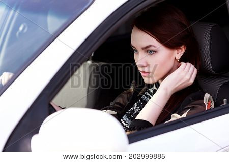 Beautiful young woman driver in a car