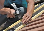 close on hand of a roofer nailing slats on a roof for renovation poster