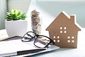 Business, finance, saving money, banking, property loan or mortgage concept :  Wood house model, coins, eyeglasses and saving account book or financial statement on office desk table poster