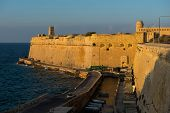 Ancient walls and buildings of Valetta fortification in late afternoon lights. Malta poster