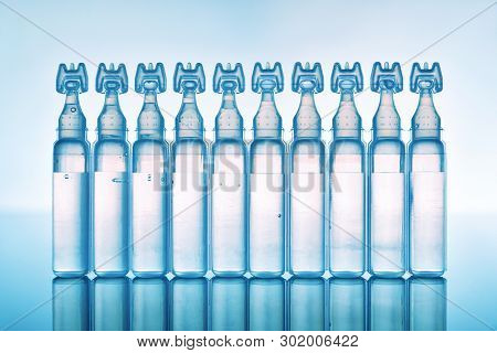 Artificial Tears Eye Drops Encapsulated In Plastic Pipettes And Reflected On Glass Table With Blue B