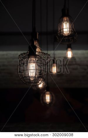 Industrial Style Wire Lamps With Filaments Glowing Inside Glass Light Bulbs In Darkness. Shiny Light