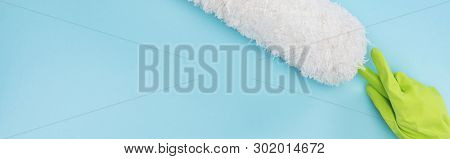 panoramic shot of cleaner in green rubber glove holding duster on blue background poster