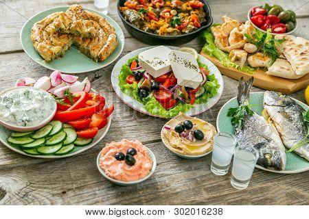 Selection Of Traditional Greek Food - Salad, Meze, Pie, Fish, Tzatziki, Dolma On Wood Background,
