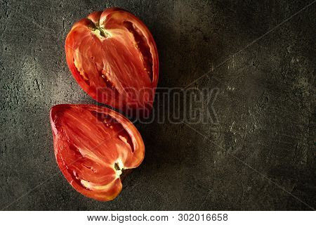 Halved Organic Red Bull's Heart Heirloom Tomato On Rustic Dark Background. Superfood Healthy Eating