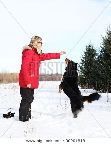 Woman giving treats to her dog during a winter day poster