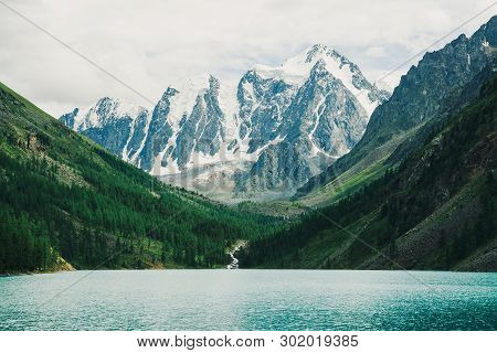Wonderful Giant Snowy Mountains. Creek Flows From Glacier Into Mountain Lake. Shine Water In Highlan